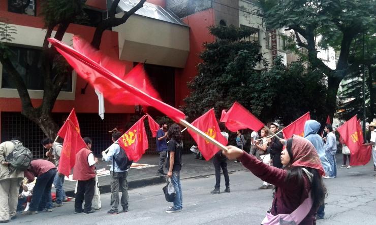Militante comunista. Agita su bandera frente a la representación del gobierno del Estado de Guerrero en la Ciudad de México, en la protesta del Partido Comunista de México por la masacre de seis estudiantes y desaparición de 47 de la Normal Rural de Ayotzinapa.  Foto: Alberto Buitre, 5 de octubre de 2014.